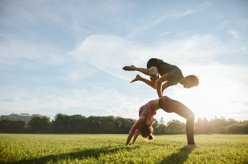 Acroyoga in the middle of a field. One figure vaults over the other.